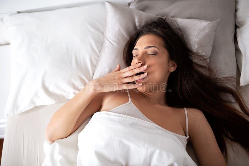 Όμορφο κορίτσι που χασμουριέται στο θερμό κρεβάτι της στοκ φωτογραφία