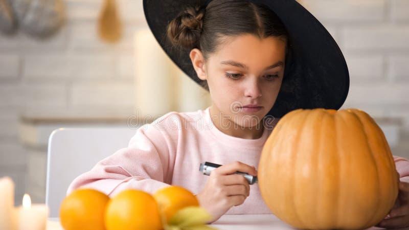 Όμορφο μικρό κορίτσι που κατασκευάζει την κολοκύθα γρύλων και που προετοιμάζεται για το κόμμα παραμονής αποκριών στοκ εικόνες