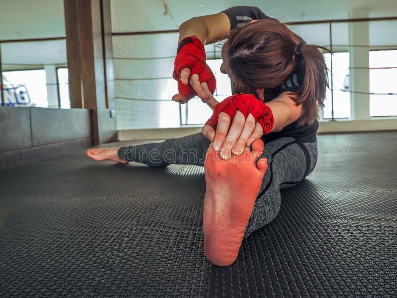 Όμορφο μυϊκό κορίτσι στις γκρίζες περικνημίδες που κάνουν το τέντωμα Αθλητική γυμναστική στο βιομηχανικό ύφος στοκ φωτογραφία