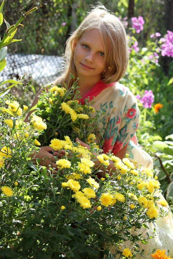 Όμορφο ξανθό μικρό κορίτσι με το μακρυμάλλες μυρίζοντας λουλούδι στοκ εικόνα
