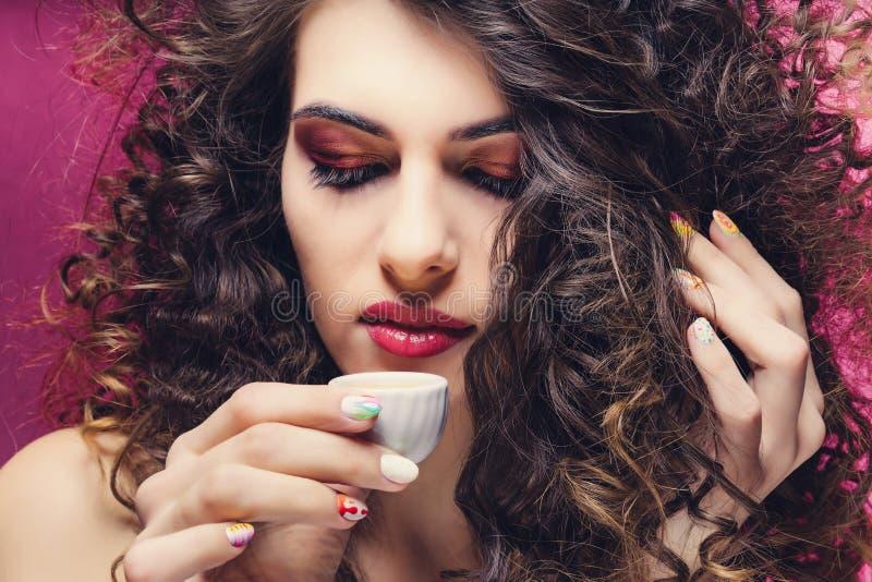 Όμορφο σγουρό κορίτσι με τη ζωηρόχρωμη κατανάλωση μανικιούρ από ένα πολύ μικρό φλυτζάνι στοκ φωτογραφία με δικαίωμα ελεύθερης χρήσης