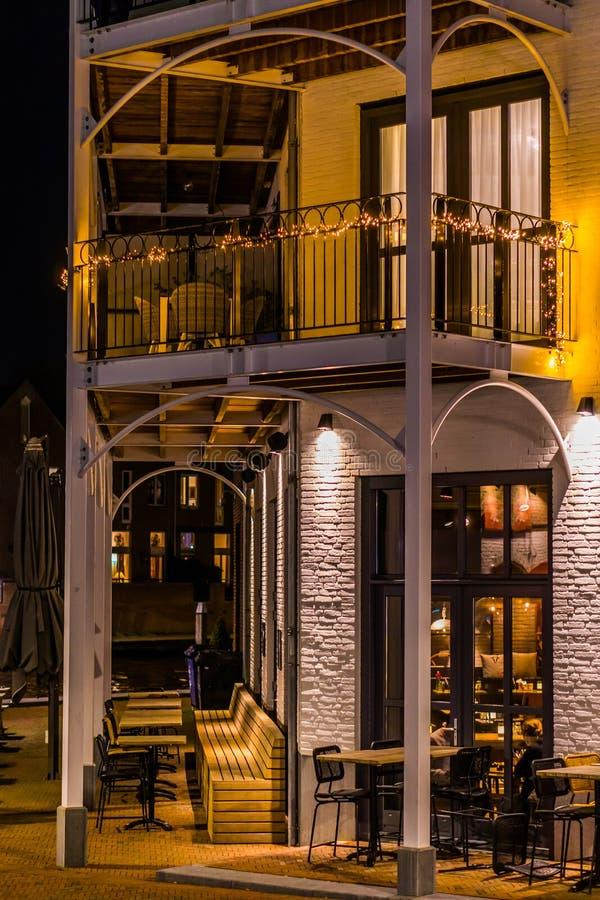 Όμορφο σύγχρονο άσπρο ολλανδικό κτήριο με ένα μπαλκόνι, τα καθίσματα πεζουλιών και τα σύνολα σαλονιών, αρχιτεκτονική πόλεων τή νύ στοκ φωτογραφία