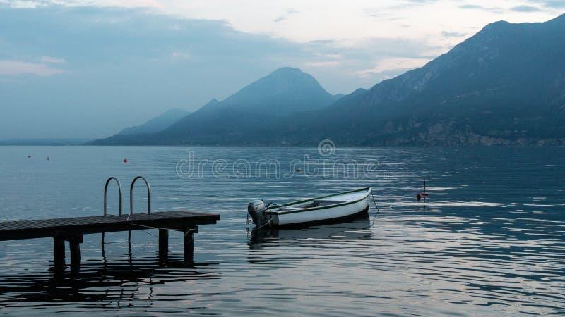 Όμορφο τοπίο στη λίμνη Garda στην Ιταλία Βάρκα κοντά στην αποβάθρα στην επιφάνεια νερού του νερού Τα μπλε χρώματα στοκ εικόνα με δικαίωμα ελεύθερης χρήσης