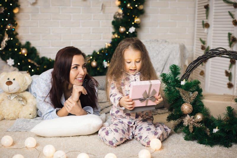 Όμορφο χαμογελώντας κορίτσι που ανοίγει το μαγικό κιβώτιο με το δώρο Χριστουγέννων στοκ εικόνες