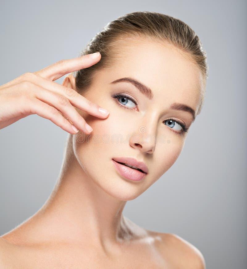Όμορφο πρόσωπο της νέας γυναίκας με το τέλειο δέρμα στοκ εικόνες