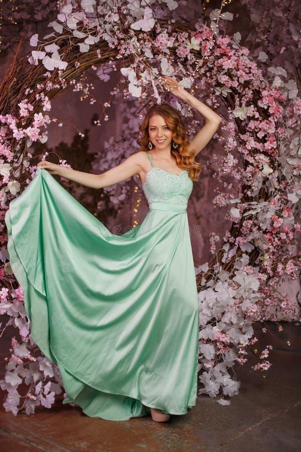 Όμορφο πρότυπο γυναικών σε ένα μέντα-χρωματισμένο φόρεμα σε ένα ανθισμένο υπόβαθρο άνοιξη Κορίτσι ομορφιάς με μια ζάλη makeup και στοκ εικόνα