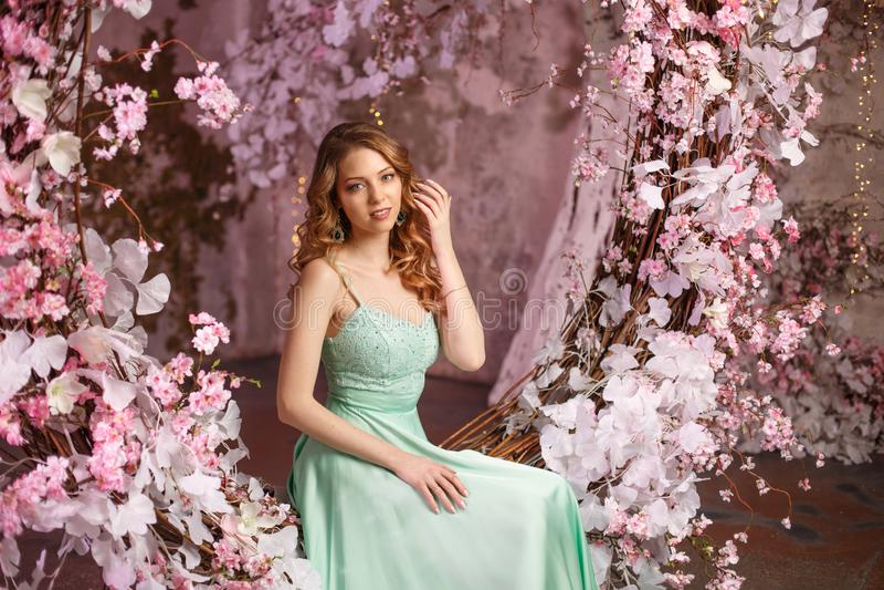 Όμορφο πρότυπο γυναικών σε ένα μέντα-χρωματισμένο φόρεμα σε ένα ανθισμένο υπόβαθρο άνοιξη Κορίτσι ομορφιάς με μια ζάλη makeup και στοκ εικόνες