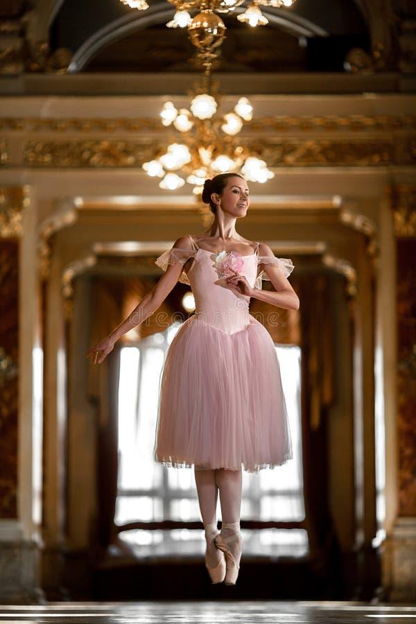 Όμορφο ballerina που χορεύει και που πηδά σε μια πολυτελή αίθουσα σε ένα ρόδινο φόρεμα στοκ εικόνες