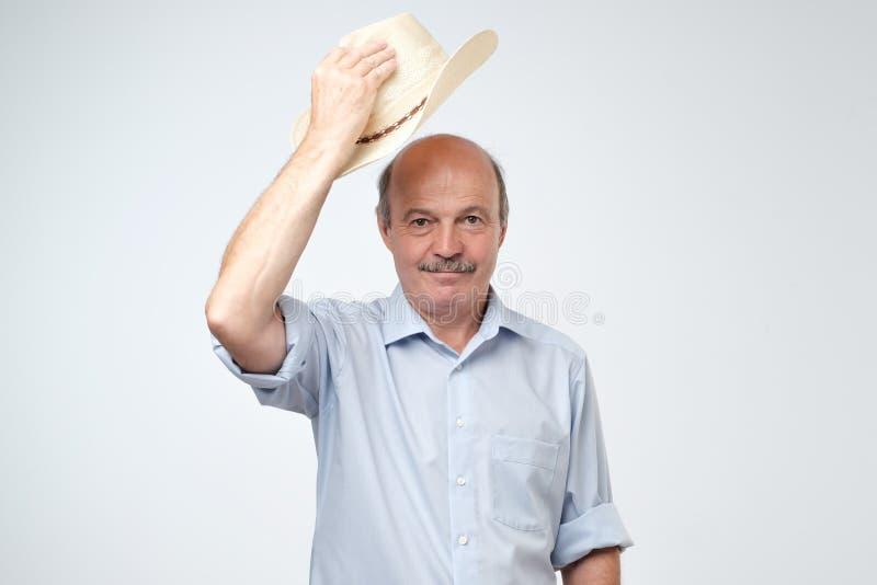 Ώριμο άτομο που κυματίζει με το καπέλο κάουμποϋ στο στούντιο Υποδοχή των φιλοξενουμένων του στοκ φωτογραφίες