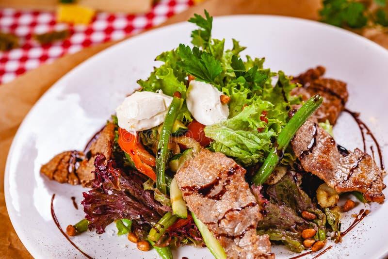 Σαλάτα με το τηγανισμένο κρέας, τα καρύδια πεύκων, τα λαχανικά και το τυρί μοτσαρελών στο άσπρο πιάτο στοκ εικόνες με δικαίωμα ελεύθερης χρήσης