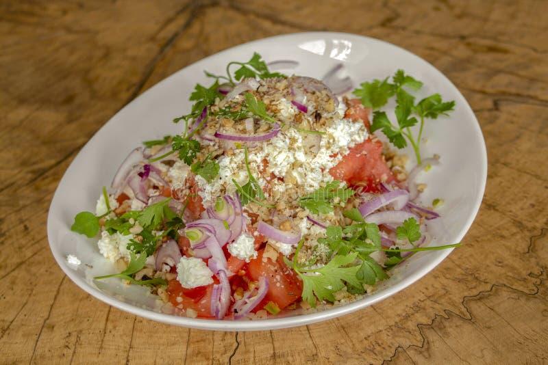 Σαλάτα σε ένα άσπρο πιάτο σε ένα ξύλινο υπόβαθρο στοκ φωτογραφία με δικαίωμα ελεύθερης χρήσης