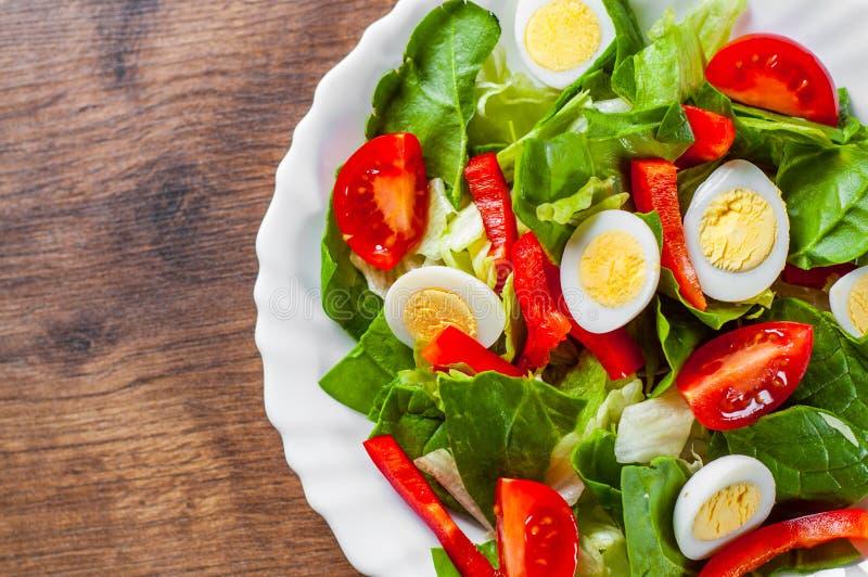 Σαλάτα σπανακιού με τα αυγά, το πιπέρι και τις ντομάτες στο άσπρο πιάτο στον ξύλινο πίνακα στοκ φωτογραφία με δικαίωμα ελεύθερης χρήσης