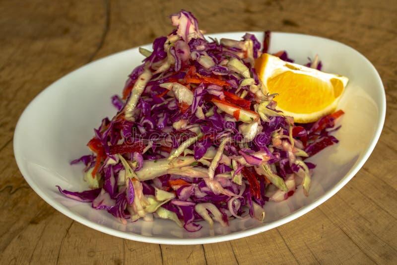 Σαλάτα φθινοπώρου σε ένα άσπρο πιάτο σε ένα ξύλινο υπόβαθρο στοκ εικόνες