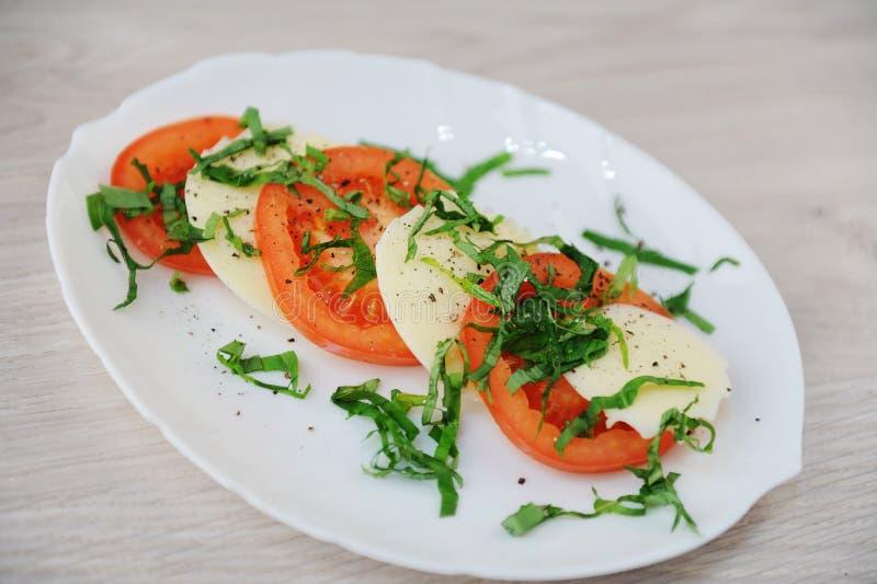 Σαλάτα Caprese σε ένα άσπρο πιάτο Μεγάλες φέτες των ντοματών, του τυριού μοτσαρελών και των πρασίνων βασιλικού στοκ εικόνα