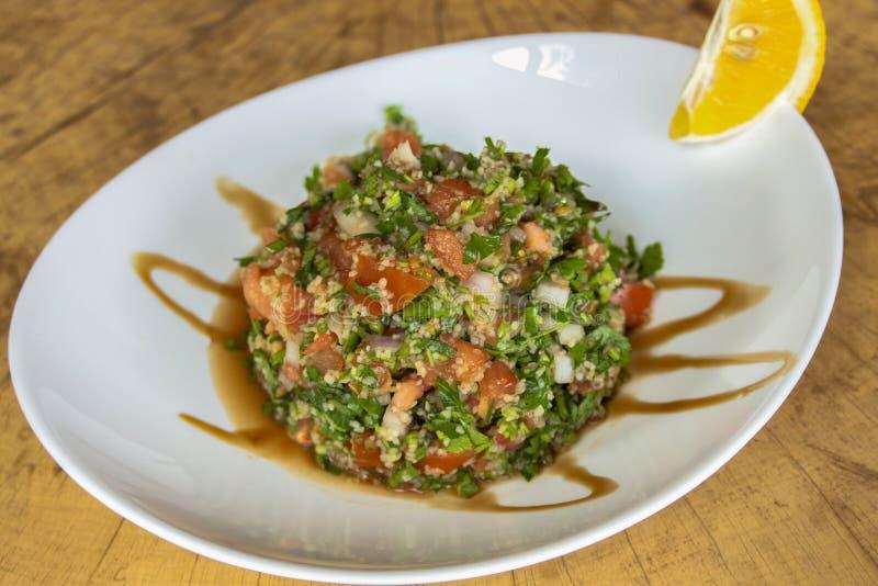 Σαλάτα Tabule Με το μαϊντανό, τις ντομάτες, το κόκκινο κρεμμύδι, το καπούλι ζώου πανεριών, το χυμό ροδιών και το πρόσφατα συμπιεσ στοκ εικόνα