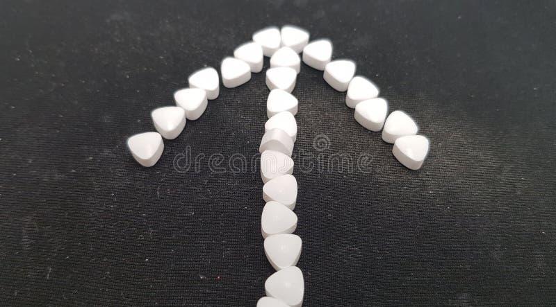 Σημάδι βελών φιαγμένο από μικρή άσπρη καραμέλα μεντών στο μαύρο μαξιλάρι ποντικιών υπολογιστών στοκ εικόνα με δικαίωμα ελεύθερης χρήσης