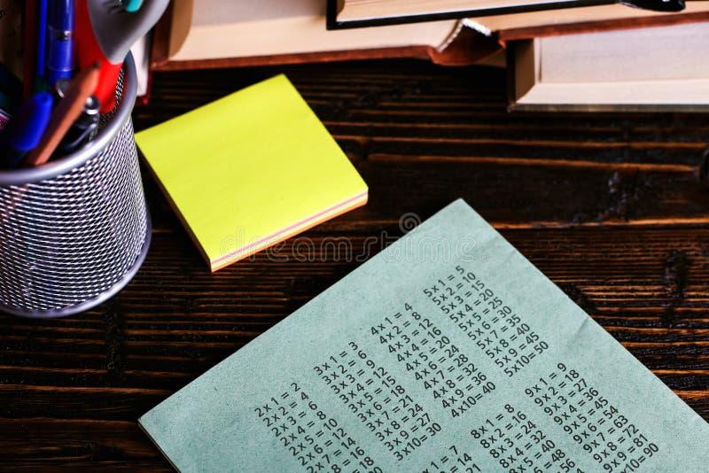 Σημειωματάριο, ανοικτές βιβλία και σχολικές προμήθειες σε έναν σκοτεινό ξύλινο πίνακα στα πλαίσια ενός πίνακα κιμωλίας Εκπαίδευση στοκ εικόνες
