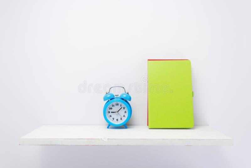 Σημειωματάριο και ξυπνητήρι στο ράφι στο άσπρο υπόβαθρο στοκ φωτογραφία