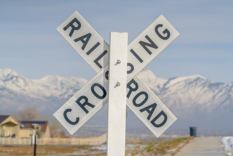 Σιδηρόδρομος που διασχίζει το σημάδι ενάντια σε ένα χιονώδες βουνό στοκ φωτογραφία με δικαίωμα ελεύθερης χρήσης