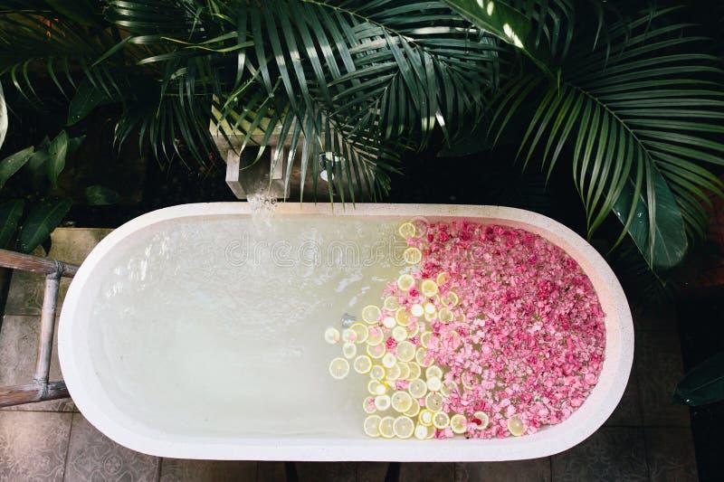 Σκάφη λουτρών που γεμίζει με το νερό με τα λουλούδια και τις φέτες λεμονιών στοκ εικόνα με δικαίωμα ελεύθερης χρήσης