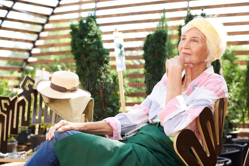 Σκεπτική ανώτερη γυναίκα που στηρίζεται στον κήπο στοκ εικόνες με δικαίωμα ελεύθερης χρήσης