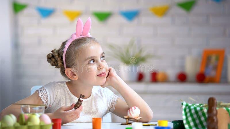 Σκεπτικό κορίτσι που ονειρεύεται για τον εορτασμό διακοπών Πάσχας, που κρατά το λαγουδάκι σοκολάτας στοκ εικόνες