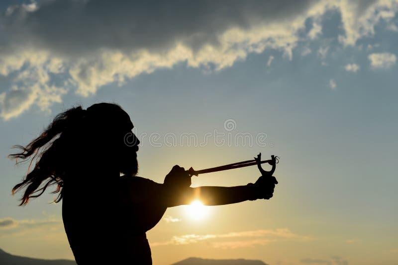 Σκιαγραφία του ατόμου που ρίχνει τη σφεντόνα στοκ φωτογραφία