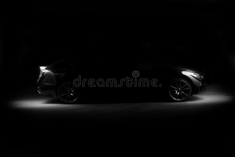 Σκιαγραφία του μαύρου αθλητικού αυτοκινήτου με τους προβολείς στο μαύρο υπόβαθρο στοκ εικόνα με δικαίωμα ελεύθερης χρήσης