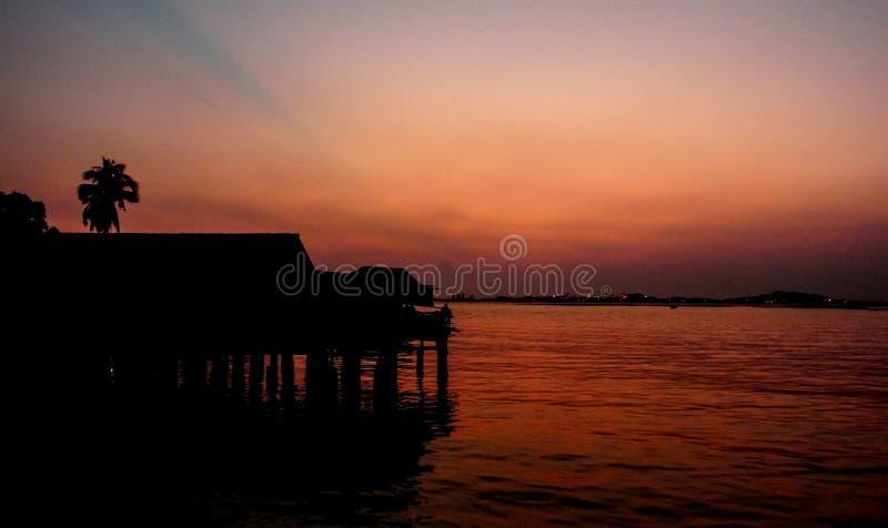 Σκιαγραφία του σπιτιού στην παραλία με τον ουρανό ηλιοβασιλέματος στοκ φωτογραφία