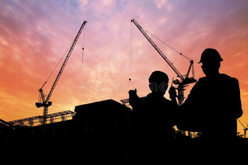 Σκιαγραφία των μηχανικών με τον εργαζόμενο στο κτήριο οικοδόμησης στοκ φωτογραφίες με δικαίωμα ελεύθερης χρήσης