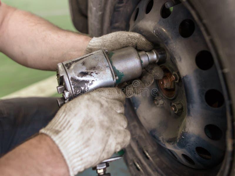 Σκλήρυνση των μπουλονιών στις ρόδες των αυτοκινήτων στο εργαστήριο στοκ εικόνα με δικαίωμα ελεύθερης χρήσης