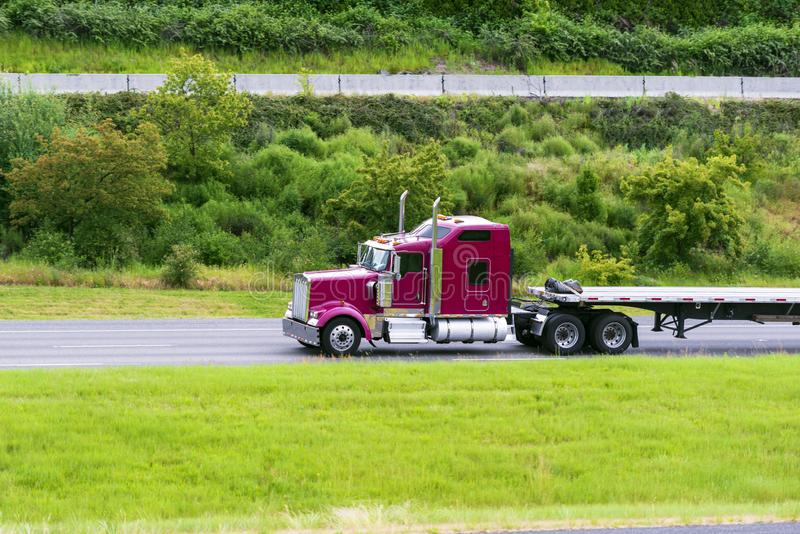 Σκούρο κόκκινο μεγάλο κλασικό αμερικανικό ημι φορτηγό καπό εγκαταστάσεων γεώτρησης με την κενή επίπεδη οδήγηση ρυμουλκών κρεβατιώ στοκ φωτογραφία με δικαίωμα ελεύθερης χρήσης