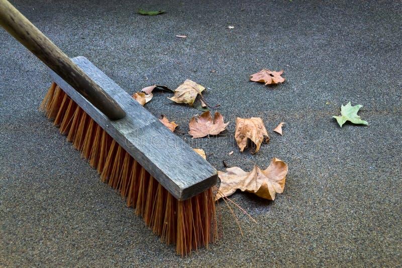 Σκούπισμα επάνω στα φύλλα φθινοπώρου στοκ εικόνα