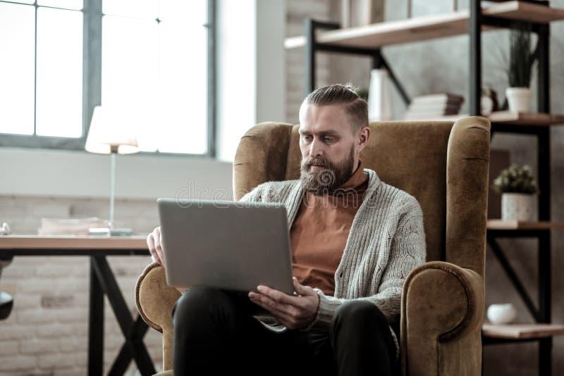 Σκοτεινός-μαλλιαρός ιδιωτικός σύμβουλος που χρησιμοποιεί το lap-top του εργαζόμενος στοκ εικόνα με δικαίωμα ελεύθερης χρήσης