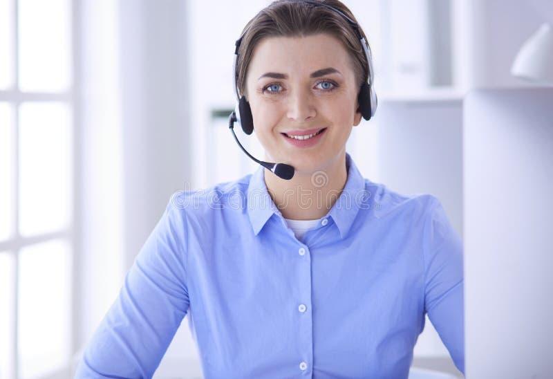 Σοβαρή αρκετά νέα γυναίκα που εργάζεται ως τηλεφωνικός χειριστής υποστήριξης με την κάσκα στην αρχή στοκ φωτογραφίες