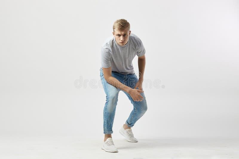 Σοβαρός ξανθός τύπος που ντύνεται σε μια άσπρη μπλούζα και τις στάσεις τζιν με τα χέρια του στα γόνατα στο άσπρο υπόβαθρο στοκ φωτογραφία με δικαίωμα ελεύθερης χρήσης
