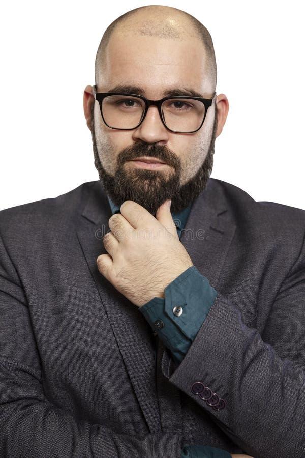 Σοβαρό νέο φαλακρό άτομο στα γυαλιά με μια γενειάδα, κινηματογράφηση σε πρώτο πλάνο η ανασκόπηση απομόνωσε το λευκό στοκ εικόνα