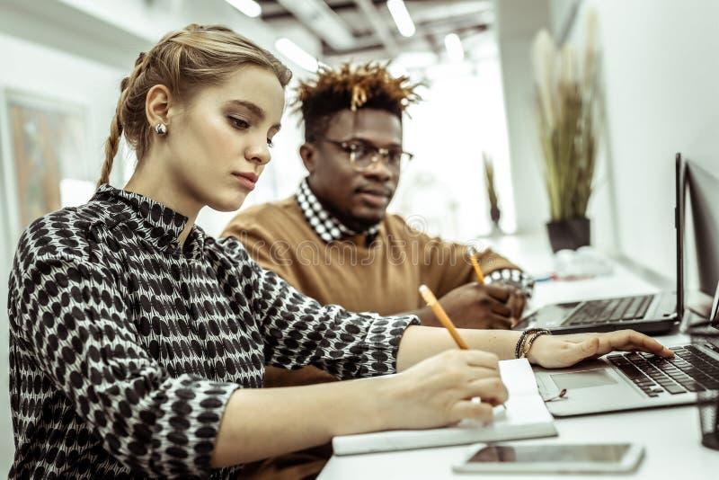 Σοβαρό προσεκτικό κορίτσι που γράφει κάτω τις πληροφορίες από την οθόνη lap-top στοκ εικόνες