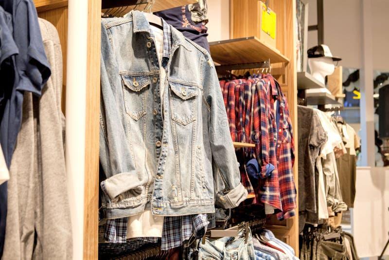 Σορτς, πουκάμισα, μπλούζες και σακάκι στο ράφι μαγαζιό Μοντέρνα ενδύματα στα ράφια στο κατάστημα Προθήκη, πώληση, αγορές στοκ εικόνες