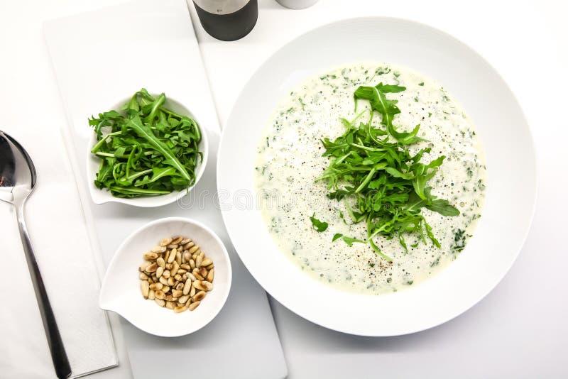 Σούπα κρέμας με τα καρύδια arugula και πεύκων σε ένα άσπρο κύπελλο στοκ εικόνες