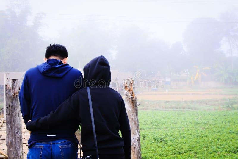 Σύζυγος που αγκαλιάζει το σύζυγο για να ενθαρρύνει ο ένας τον άλλον για να περπατήσει μαζί στην υδρονέφωση της δροσερής ομίχλης στοκ εικόνες