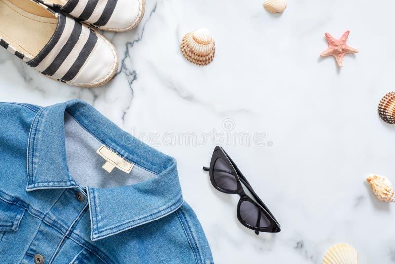 Σύνθεση θερινών διακοπών Μοντέρνο σακάκι τζιν, γυαλιά ηλίου, ριγωτά σανδάλια, θαλασσινά κοχύλια, αστέρι θάλασσας στο μαρμάρινο υπ στοκ φωτογραφία