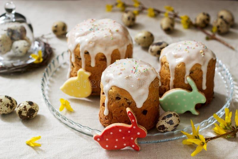 Σύνθεση Πάσχας των κέικ Πάσχας, των μπισκότων, των αυγών και των λουλουδιών forsythia Αγροτικό ύφος στοκ εικόνες