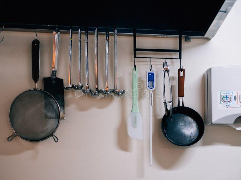 Σύνολο ένωσης σκευών για την κουζίνα στον τοίχο στο εστιατόριο Sapporo Ramen στις αγορές Arcade Tanukikoji στοκ εικόνα