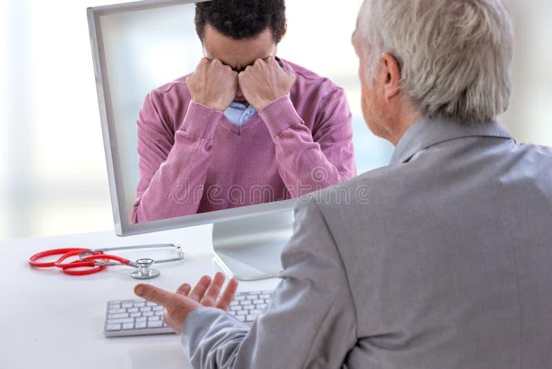 Σύνοδος ψυχολόγων για τη οθόνη υπολογιστή Τηλεϊατρική ή telehealth για έναν καταθλιπτικό νεαρό άνδρα στοκ φωτογραφία με δικαίωμα ελεύθερης χρήσης