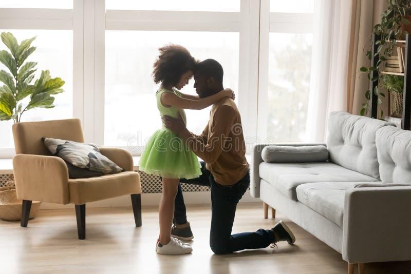 Στοργικός αγαπώντας μαύρος μπαμπάς που αγκαλιάζει τη στάση κοριτσιών παιδιών στο γόνατο στοκ εικόνες
