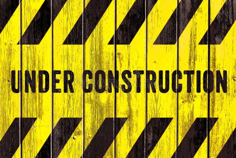 Στο πλαίσιο του κειμένου προειδοποιητικών σημαδιών κατασκευής με τα κίτρινα μαύρα λωρίδες που χρωματίζονται στο ξύλινο ευρύ υπόβα στοκ φωτογραφία