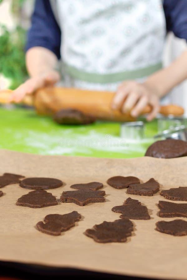 Στο πρώτο πλάνο, πιεσμένες μορφές από τη ζύμη με τις φόρμες Στο υπόβαθρο, τα χέρια του παιδιού που κυλά μια ζύμη με έναν ξύλινο κ στοκ εικόνες