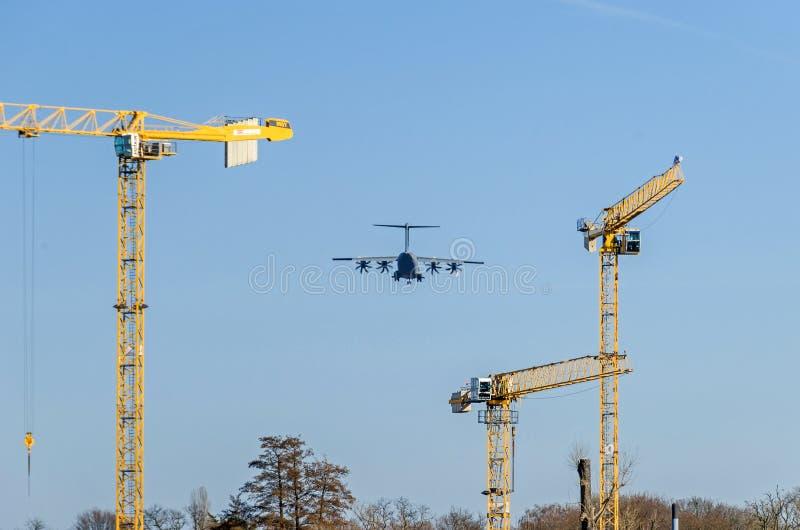 Στρατιωτικό αεροπλάνο που προσγειώνεται στον αερολιμένα Βερολίνο-Tegel πέρα από τη κατοικήσιμη περιοχή στοκ εικόνα
