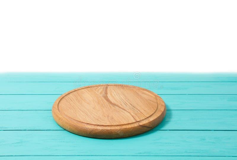 Στρογγυλός ξύλινος τέμνων πίνακας πιτσών στον μπλε ξύλινο πίνακα που απομονώνεται στο άσπρο υπόβαθρο Τοπ διάστημα άποψης και αντι στοκ φωτογραφία